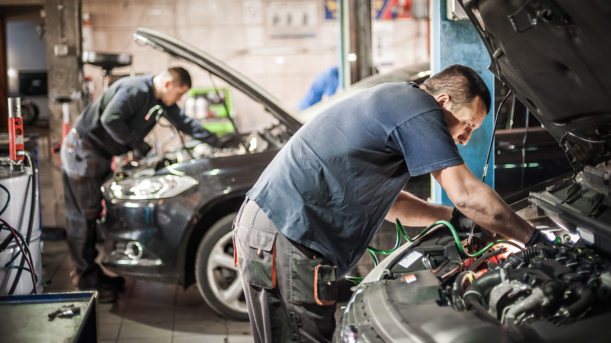 two men working under hood of two different cars